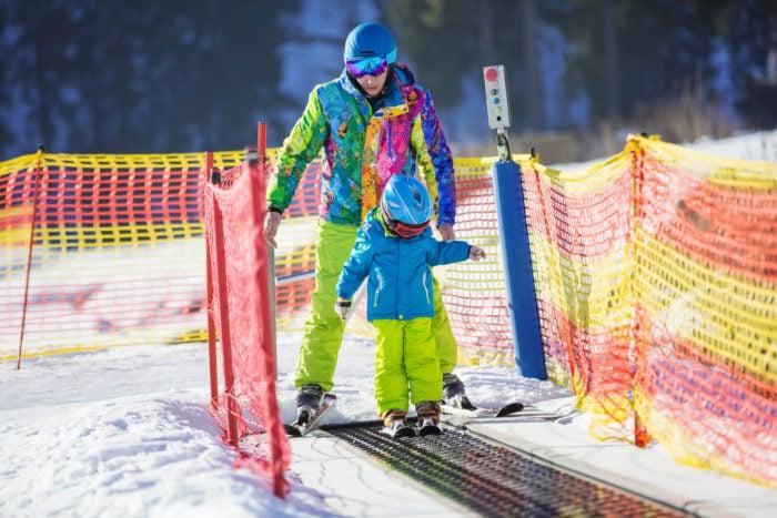 Bambino sulla neve usa tappeto di risalita della Skiarea di Livigno